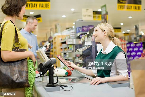 cashier and customers at supermarket checkout - cash register stock pictures, royalty-free photos & images