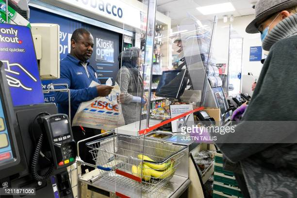 Cashier at a Tesco supermarket works behind a protective perspex barrier in Croydon, south London on May 5, 2020 as life in Britain continues during...