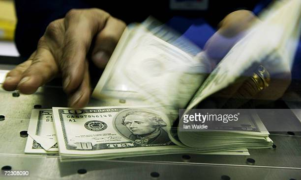 Cashier at a Travelex Bureau de Change counts U.S. Dollars in exchange for British pounds February 19, 2004 in London. The recent dramatic fall in...