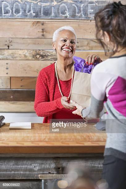 Cashier at boutique handing customer a shopping bag