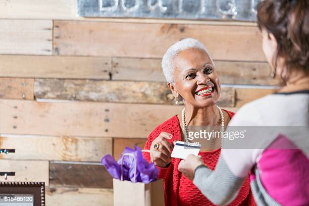cashier at boutique taking credit card from customer - happy merchant stock pictures, royalty-free photos & images