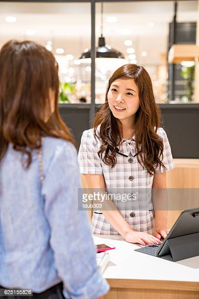 Cashier at department store taking payment by digital tablet