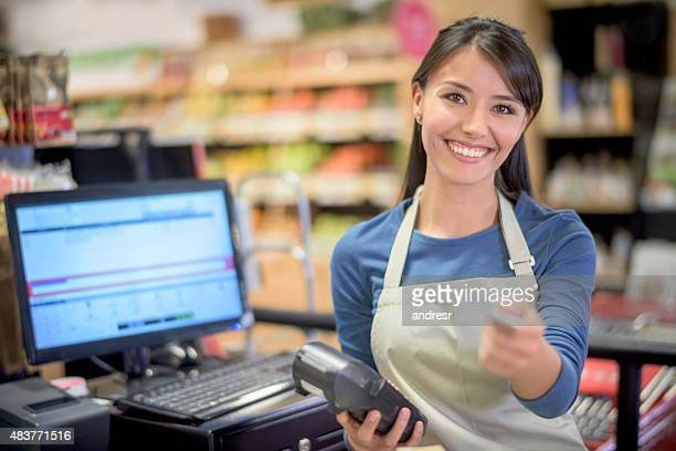 cashier at the supermarket getting a card payment - cashier stock pictures, royalty-free photos & images