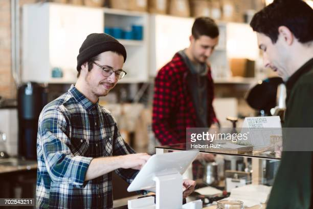 Cashier attending to customer in cafe