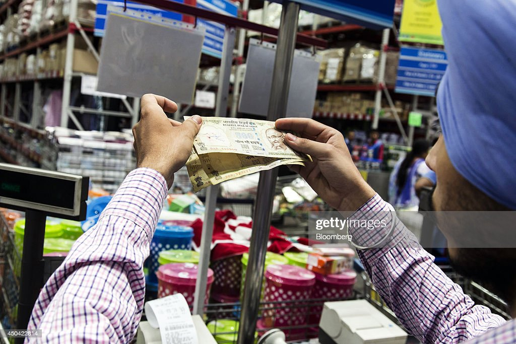 A cashier checks Indian Rupee banknotes at a checkout counter inside a Walmart India Pvt Best Price Modern Wholesale store in the town of Zirakpur on.