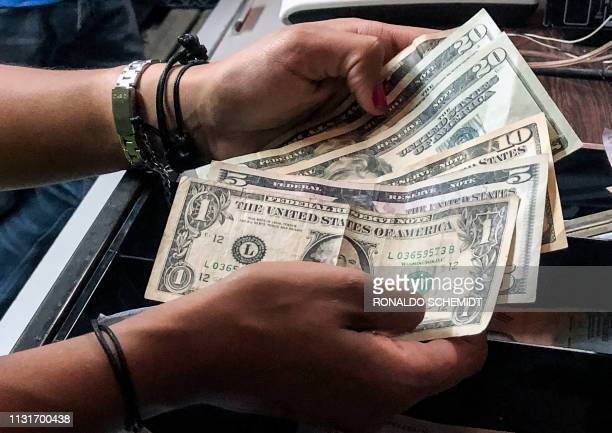 A cashier counts dollar bills at a restaurant in Caracas on March 18 2019 Whether paying for a manicure an evening gown or a liter of milk in...