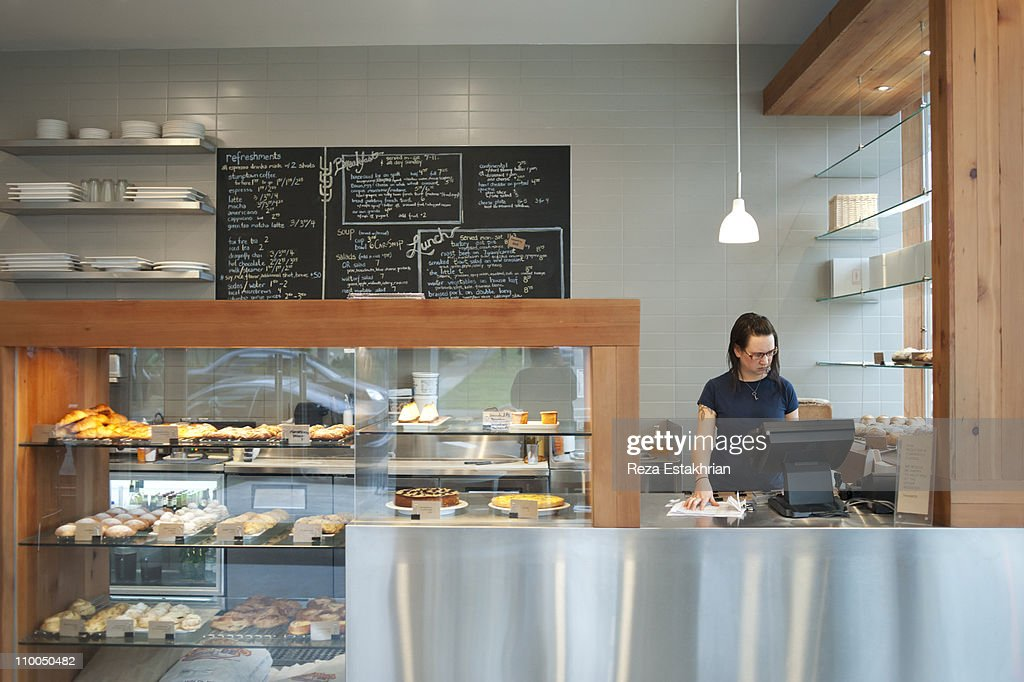 Cashier enters information at cash register : Stock Photo