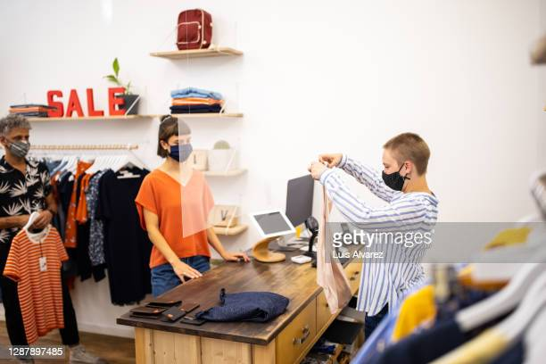cashier folding clothes purchased by customer at checkout counter - opening event stock pictures, royalty-free photos & images