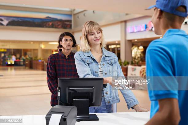 cashier giving ticket to customer at theater - hygiaphone photos et images de collection