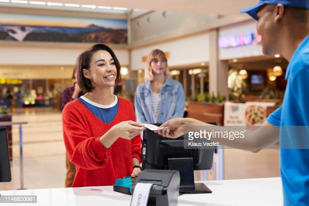 cashier giving tickets to smiling woman - hygiaphone photos et images de collection