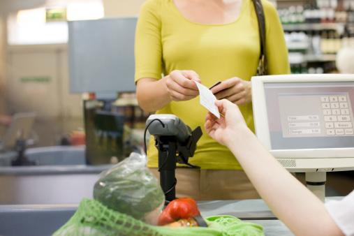Cashier handing receipt to customer 108350281