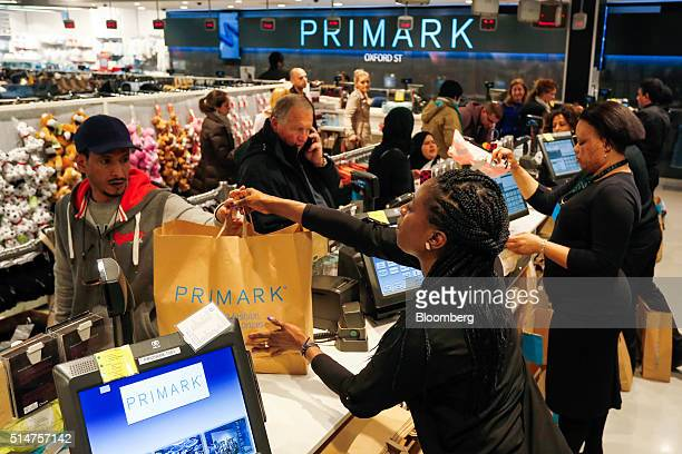 A cashier hands shopping to a customer at a Primark clothing store operated by Associated British Foods Plc on Oxford Street in London UK on Friday...