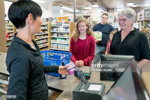 Cashier helping customers in nutrition store