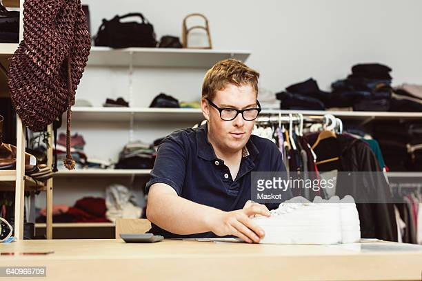cashier holding shoes on table while calculating in clothing store - disability collection stock pictures, royalty-free photos & images