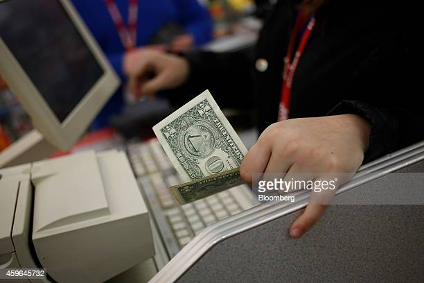 A cashier holds a US one dollar bill at the checkout inside a Kmart discount store operated Sears Holdings Corp ahead of Black Friday in Frankfort...