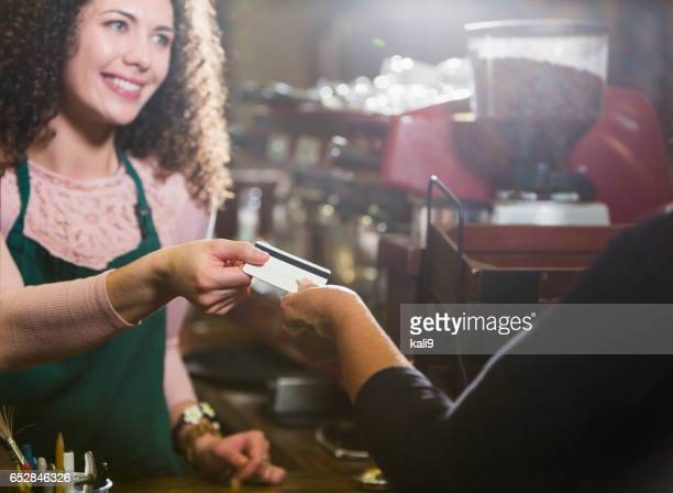 cashier in coffee shop takes payment card from customer - gift card imagens e fotografias de stock