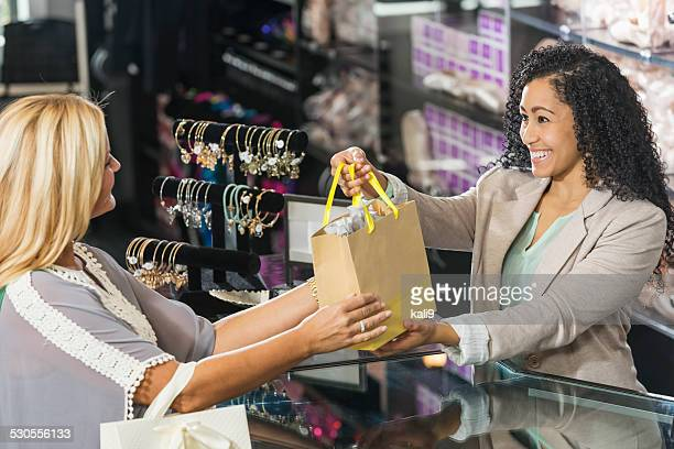 Cashier in retail store handing customer a shopping bag