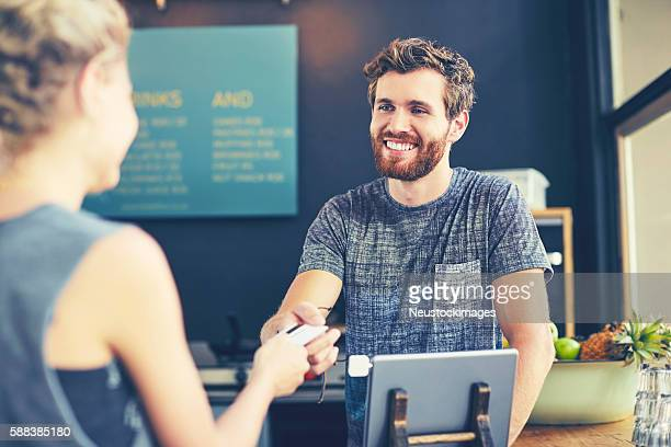 cashier looking at customer while receiving card - checkers stock photos and pictures