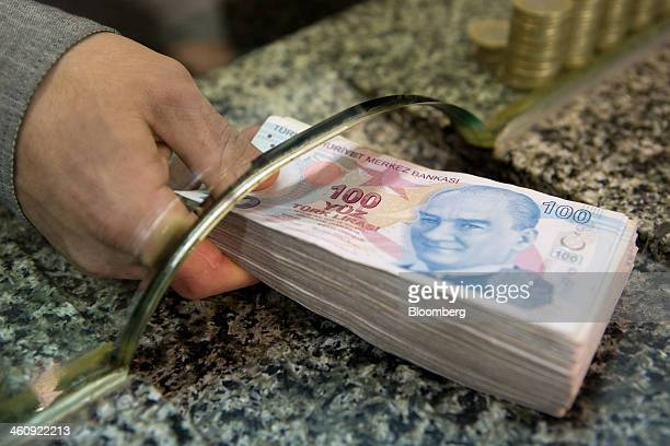A Cashier Pes Pile Of 100 Denomination Turkish Lira Banknotes Across The Counter