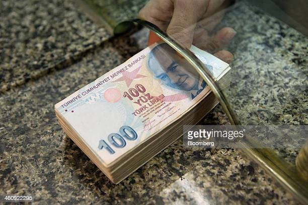 A cashier passes a pile of 100 denomination Turkish lira banknotes across the counter of a currency exchange in this arranged photograph in Istanbul...