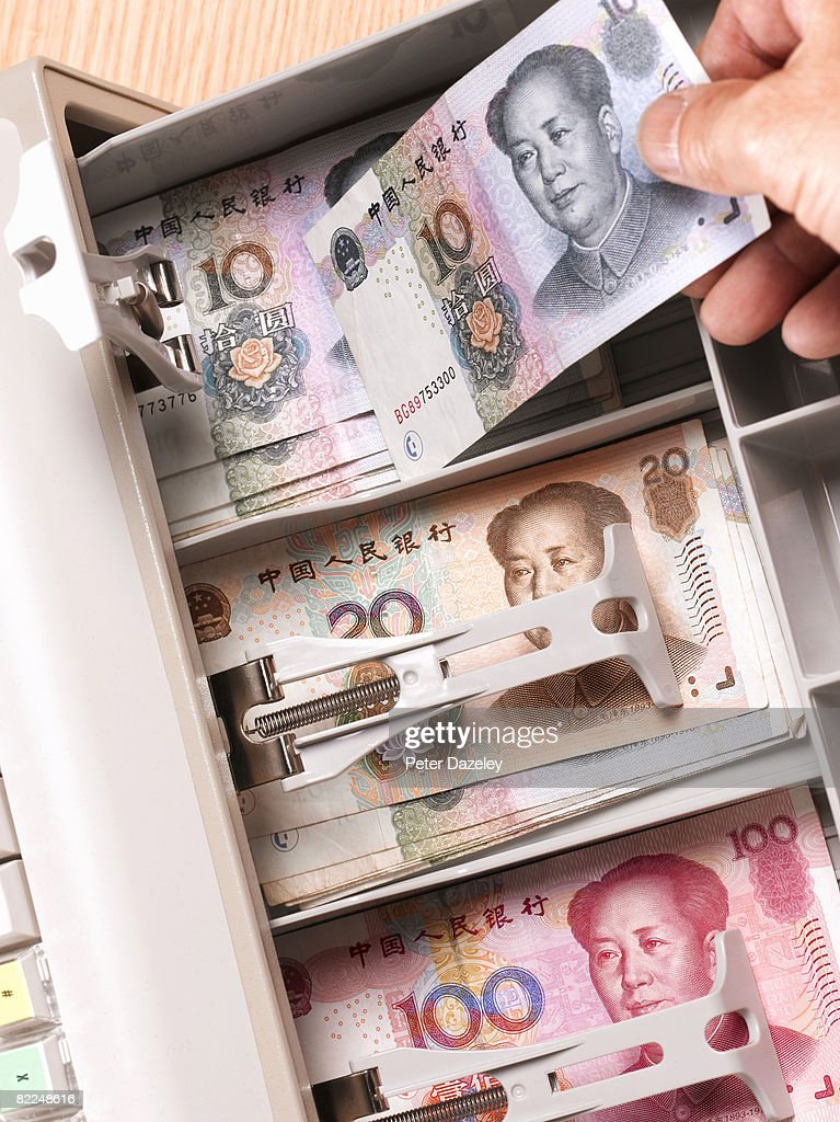 Cashier placing Chinese Yaun in Cash register : Stock Photo
