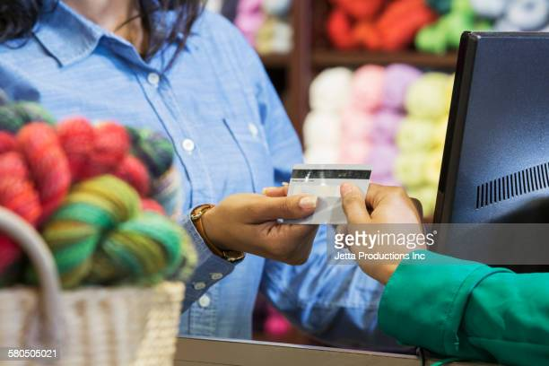 Cashier processing credit card for customer in yarn store