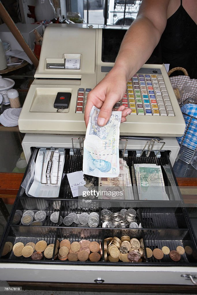 cashier-putting-money-in-cash-register-picture-id78747819