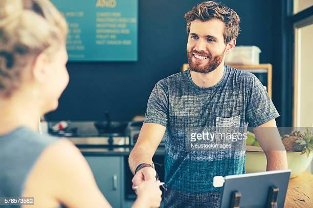 cashier receiving credit card from female customer - vendedor de loja - fotografias e filmes do acervo