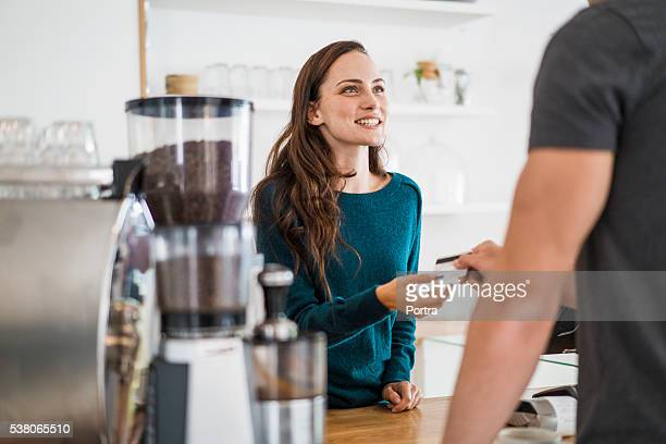 Cashier receiving payment from customer in cafe
