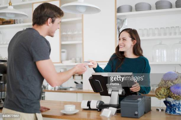 cashier receiving payment from customer in cafe - cashier stock pictures, royalty-free photos & images