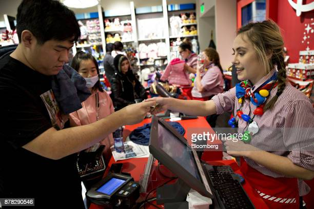 A cashier right serves a customer at a check out counter inside a Walt Disney Co store at the Fashion Outlets of Chicago mall in Chicago Illinois US...