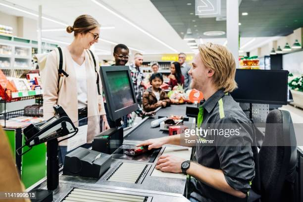 cashier ringing up customers groceries - cashier stock pictures, royalty-free photos & images