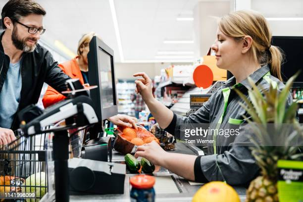 cashier ringing up mature couple's groceries bill - cash register stock pictures, royalty-free photos & images