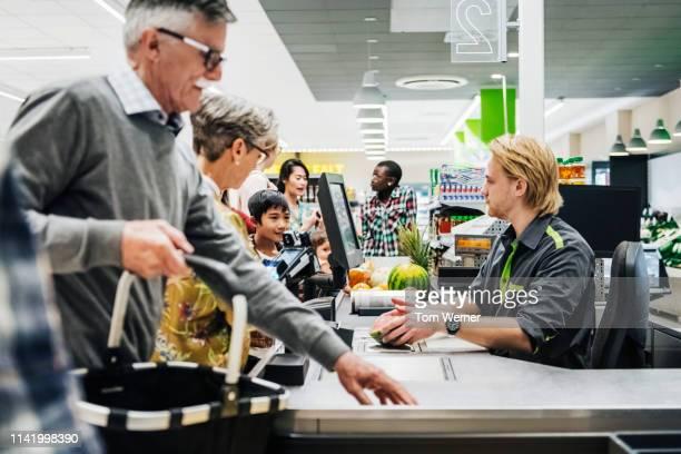 cashier ringing up senior couple's groceries - kassierer stock-fotos und bilder
