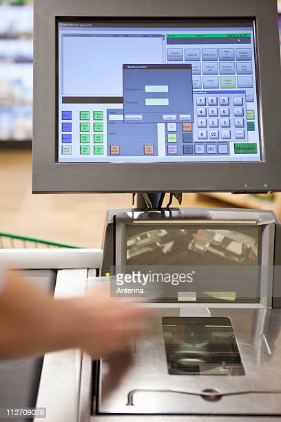 A cashier scanning groceries at a supermarket, focus on hand