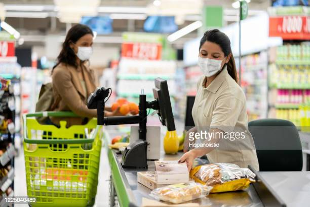 cashier scanning products at a grocery store wearing a facemask - prevention imagens e fotografias de stock