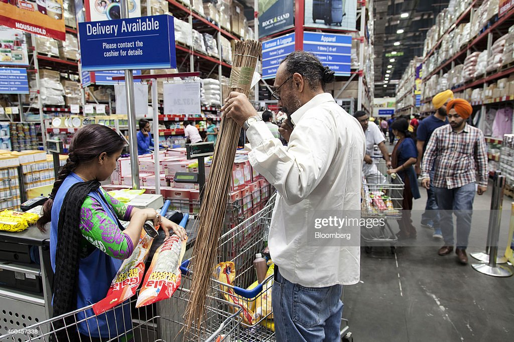 A cashier scans brooms as a customer waits at a checkout counter inside a Walmart India Pvt Best Price Modern Wholesale store in the town of Zirakpur.