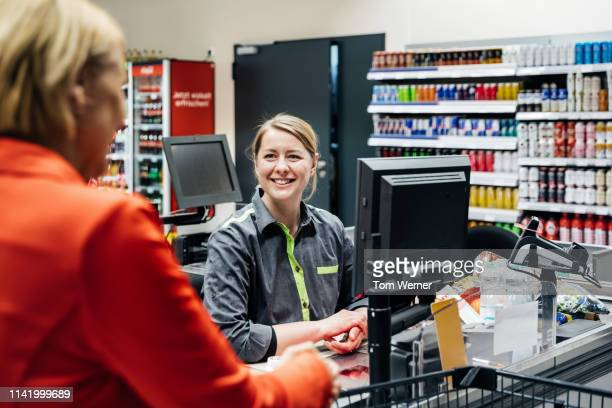 cashier smiling at customer buying groceries - cashier stock pictures, royalty-free photos & images