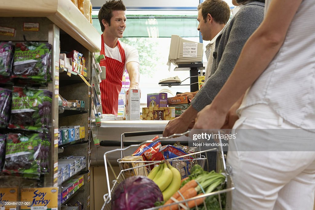 Cashier smiling at customer on checkout line in supermarket, close-up : Stock Photo