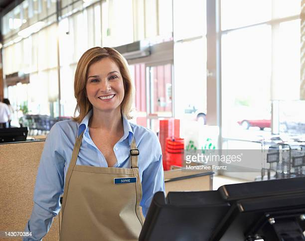 cashier standing at till in supermarket - name tag stock photos and pictures