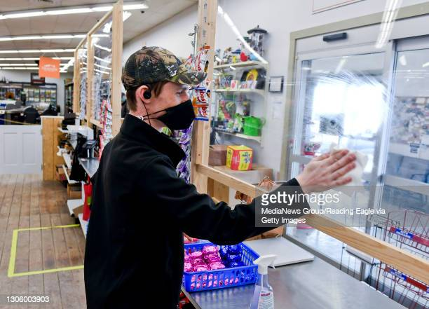 Cashier Stephen Maurek cleans off the plexiglass partition at the cash register. At Weaver's Ace Hardware on Fleetwood Lyons Road in Richmond...