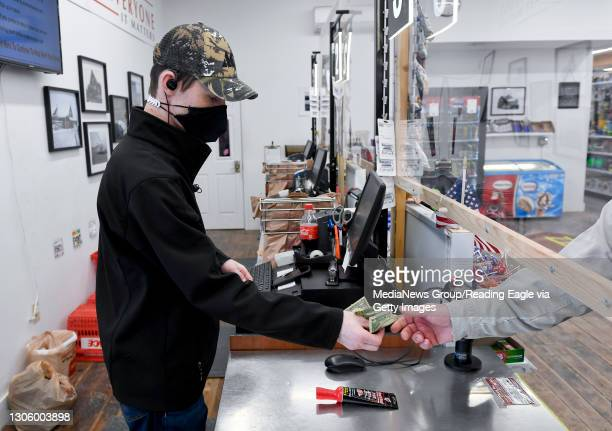 Cashier Stephen Maurek is handed money by a customer under an opening in the plexiglass partition at the cash registers. At Weaver's Ace Hardware on...