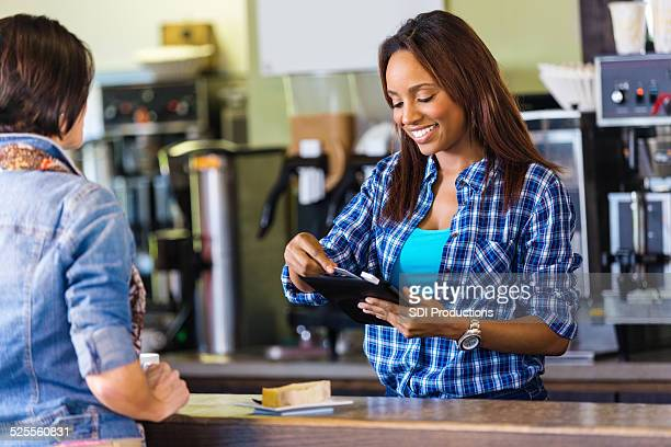 Cashier swiping credit card with digital tablet reader