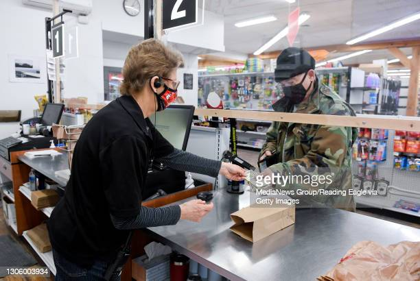 Cashier Tracy Burkert hands customer Tom Kemery his change through an opening under the plexiglass partition. At Weaver's Ace Hardware on Fleetwood...