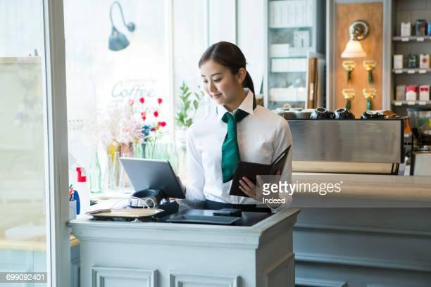 Cashier using digital tablet in restaurant