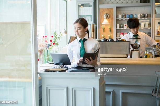 Cashier using digital tablet in restaurant