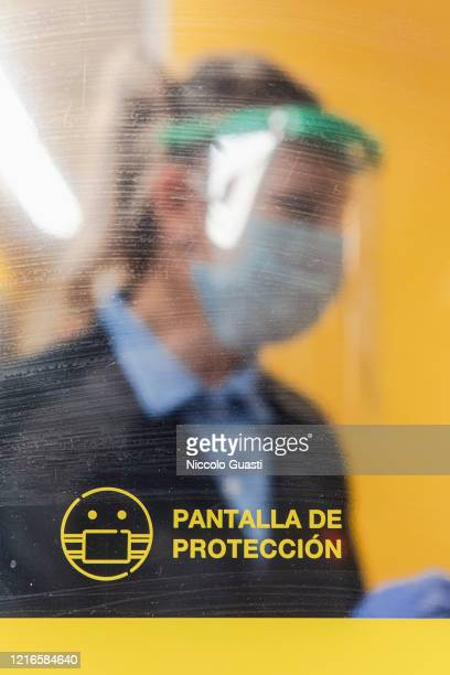 Cashier Vanesa behind a Protection screen a measure of protection and distancing at a supermarket on April 03 2020 in Various Cities Spain Spain...