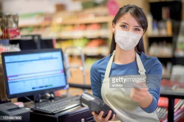 kassiererträgt eine gesichtsmaske im supermarkt und bekommt eine kartenzahlung - kassierer stock-fotos und bilder