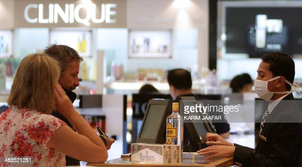 A cashier wearing a protective mask serves customers at the duty free shopping zone of the airport in Doha on May 5 2009 The number of swine flu...