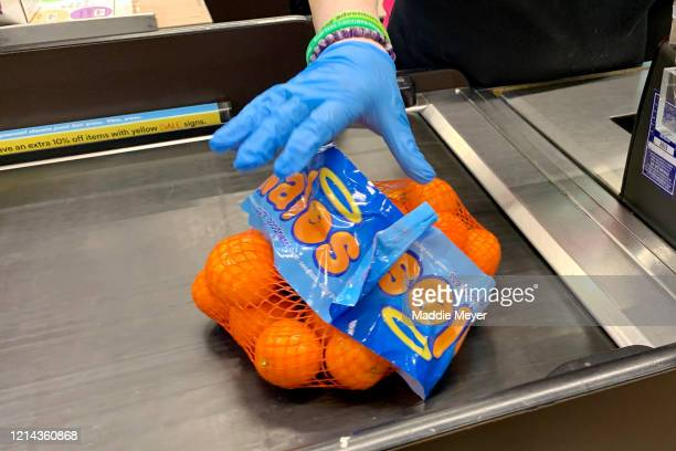 Cashier wears gloves at Whole Foods on March 23, 2020 in Cambridge, Massachusetts. Massachusetts Governor Charlie Baker ordered all non-essential...